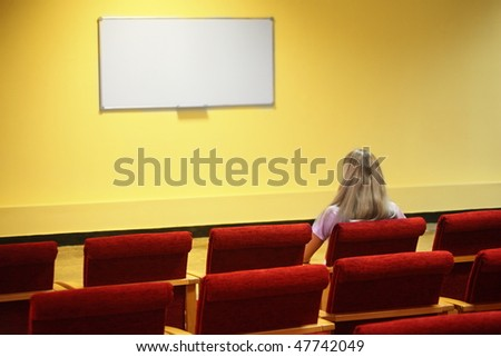 woman sitting in a chair in a first row of empty presentation hall. screen in out of focus. focus on a woman. - stock photo