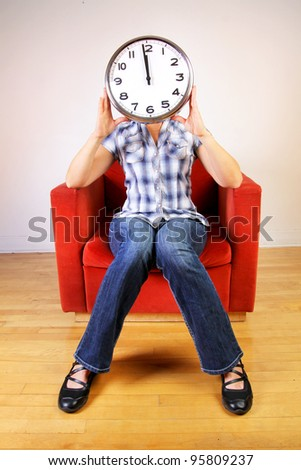 Woman sitting in a orange sofa holding a clock set at midday or midnight in front of her face