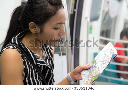 woman sitting in a train and is studying the route map - stock photo