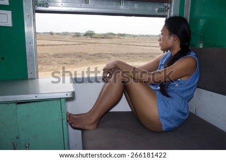 woman sitting in a train and looking from window - stock photo