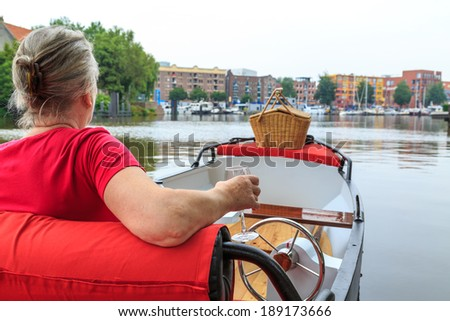 Woman sitting in boat with picnic basket - stock photo