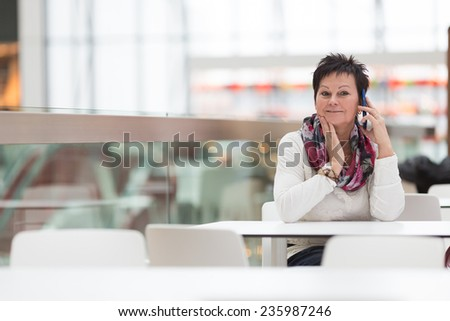 Woman sitting in cafe and calling with mobile phone. Cafe city lifestyle woman on phone. Business concept - businesswoman talking on the phone in restaurant. - stock photo