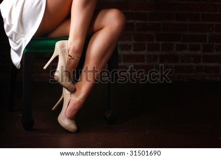 Woman sitting in chair with legs and stilettoes - stock photo