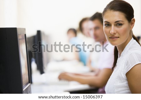 Woman sitting in computer room with people in background - stock photo