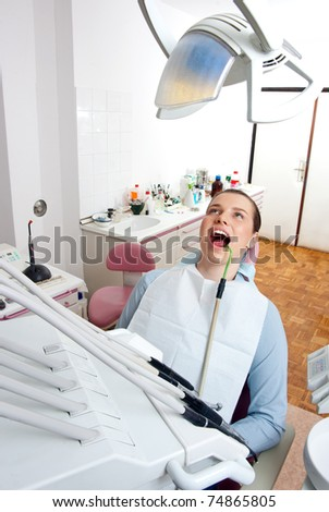 woman sitting in dentist chair with suction tube - stock photo
