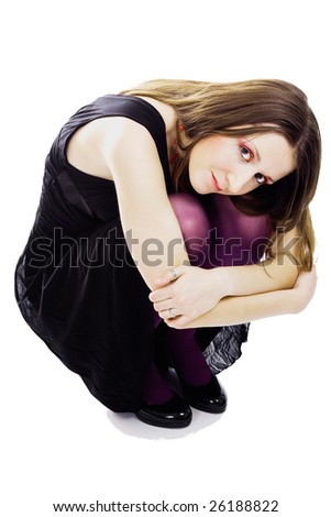 Woman sitting in dress and violet pantyhose on white background