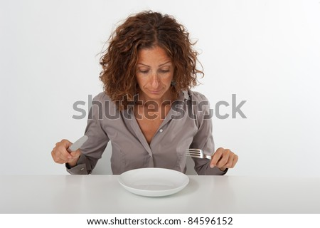 Woman sitting in front of an empty dish looking at it. Diet concept. You can place the food you prefer in the plate. - stock photo