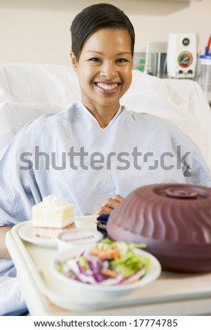 Woman Sitting In Hospital Bed With A Tray Of Food - stock photo