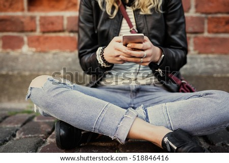 Woman sitting in lotus position in city and using smartphone