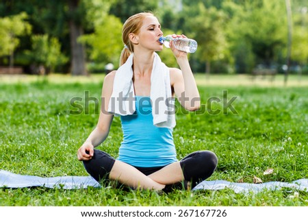 Woman sitting in the park and drinking water after exercise.Refreshment after exercise - stock photo