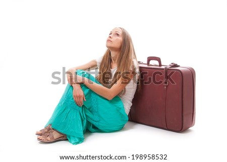 Woman sitting near a suitcase, isolated on white background - stock photo