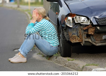 Woman sitting near the car after accident - stock photo