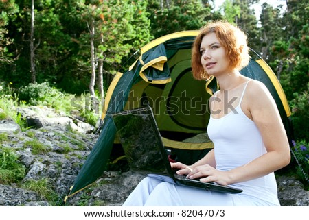 woman sitting next to a tent with a laptop - stock photo