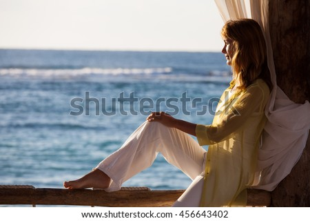 woman sitting on a balcony at sunset on the sea