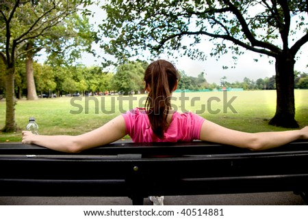 woman sitting on a bench looking at a landscape - stock photo