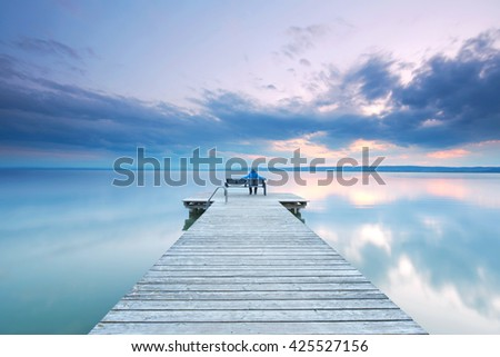 woman sitting on a bench on wooden pier at Lake Neusiedl at sunrise near Podersdorf, Burgenland, Austria