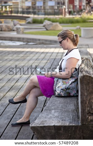 Woman sitting on a bench reading in Western Harbour, Malmoe - stock photo