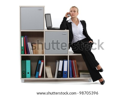 Woman sitting on a bookcase - stock photo