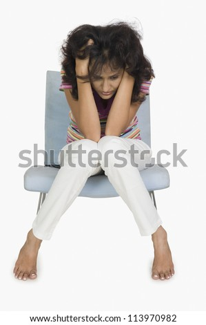 Woman sitting on a chair and looking depressed - stock photo