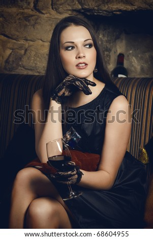 Woman sitting on a couch and holding a glass of wine - stock photo