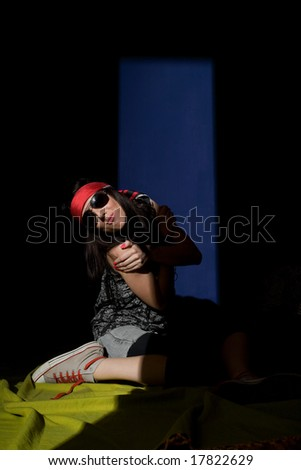 Woman sitting on a floor lit from another room with half closed door. Strong shadow