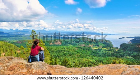 Woman sitting on a rock and enjoying the beautiful view on Vancouver Island, British Columbia, Canada - stock photo