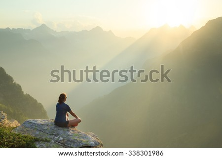 Woman sitting on a rock, enjoying the summer sunset in the mountains. - stock photo