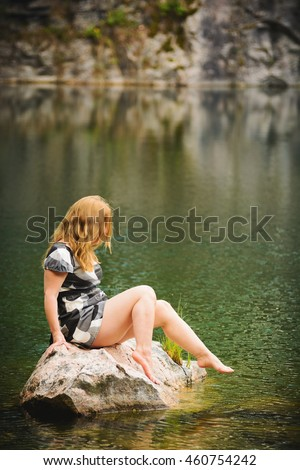 Woman sitting on a rock near lake