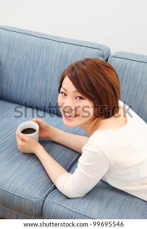 woman sitting on a sofa - stock photo