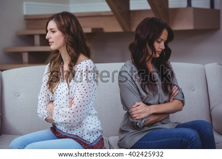 Woman sitting on a sofa and ignoring her friend after an argument