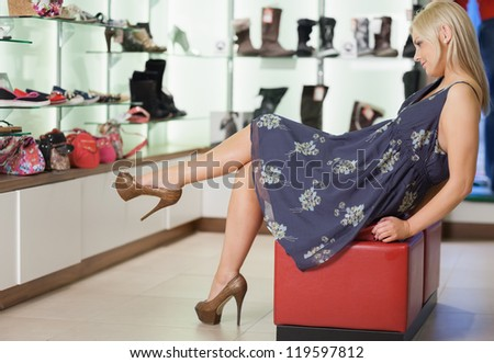 Woman sitting on a stool admiring shoes in boutique - stock photo