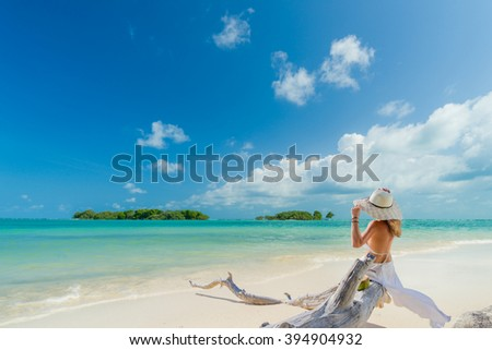 Woman sitting on a tree trunk at the beach - stock photo