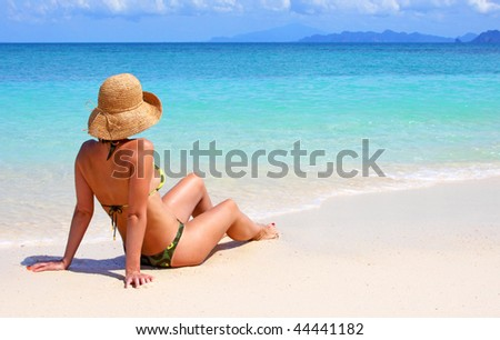 woman sitting on a tropical beach in the caribbean - stock photo