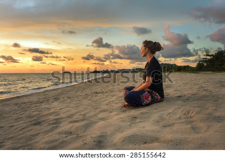 Woman sitting on beach sand and relaxing at sunset time - stock photo