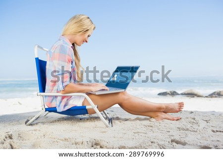 Woman sitting on beach using her laptop against website interface