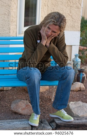 Woman sitting on bench depressed and frustrated - stock photo