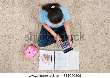 Woman Sitting On Carpet With Piggybank And Money Calculating Budget - stock photo