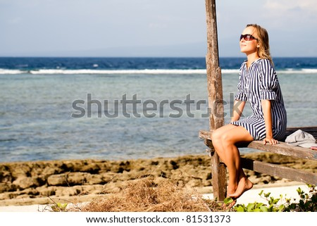 Woman sitting on deck by the sea