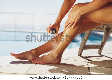 Woman sitting on deck chair by the swimming pool spraying suntan lotion onto her legs - stock photo