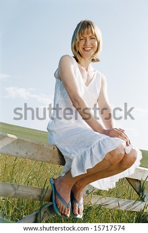 Woman sitting on fence outdoors smiling - stock photo