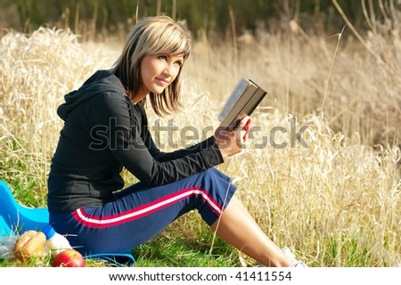 Woman sitting on grass reading a book. - stock photo
