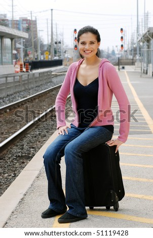 woman sitting on luggage waiting for train