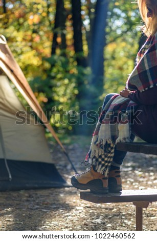 woman sitting on picnic bench wearing hiking boots outside tent on campsite on an early autumn morning