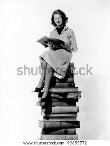 Woman sitting on pile of books - stock photo