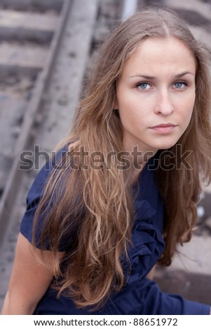 Woman sitting on rails outdoors shooting - stock photo