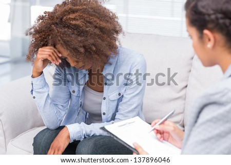 Woman sitting on sofa and crying with therapist taking notes - stock photo