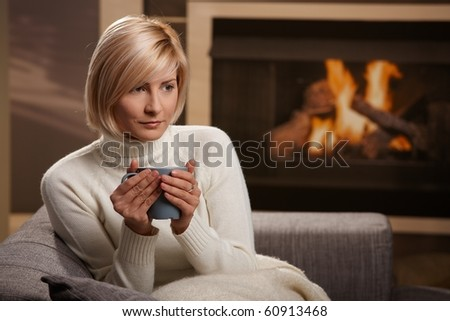 Woman sitting on sofa at home drinking hot tea, looking away. - stock photo