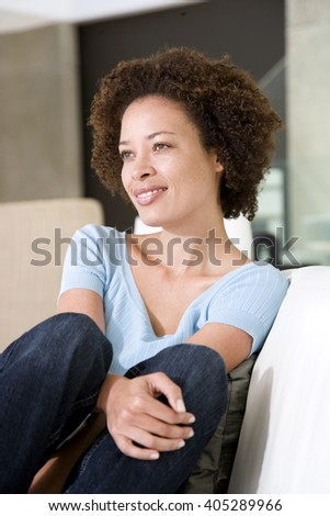 Woman sitting on sofa relaxing at home - stock photo