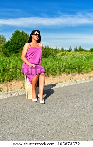 Woman sitting on suitcase on the road. - stock photo