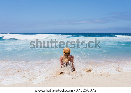Woman sitting on the beach. Attractive girl among the ocean waves. - stock photo